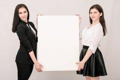 Zwei glückliche lächelnde junge Geschäftsfrauen, die großes leeres signbo tragen Stockfotos