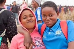 zwei gl?ckliche l?chelnde sch?ne junge M?dchen des Afrikaners umfassen Freien auf den Leuten, die oben Umhlanga-Ritus-Hintergrund lizenzfreie stockfotos
