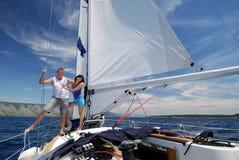 Zwei glückliche Leute, die mit dem Segelboot reisen lizenzfreies stockbild