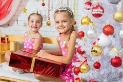 Zwei glückliche Mädchen, die auf einer Bank mit einem Weihnachtsgeschenk sitzen Stockfotografie