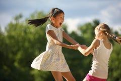 Zwei glückliche Mädchen, die in einen Kreis tanzen stockfoto
