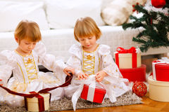 Zwei glückliche Mädchen, die Geschenke öffnen, nähern sich Weihnachtsbaum Lizenzfreies Stockfoto
