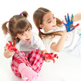 Zwei glückliche Mädchen, die mit Fingerfarben spielen Lizenzfreies Stockbild