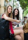 Zwei glückliche Mädchen mit Karte Stockfoto