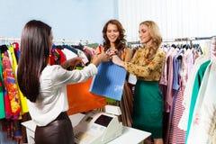 Zwei glückliche Mädchen mit Kauf nahe Heftstand stockfotos