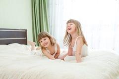 Zwei glückliche Mädchen oder Kinder, die auf Bett liegen lizenzfreie stockfotografie