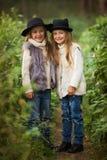 Zwei glückliche Mädchen werden gleichmäßig gekleidet: in den Pelzwesten und -hüten in den Waldkleinen Freundinnen im Park stockfoto