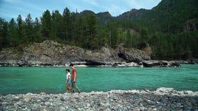 Zwei glückliche Menschen, die entlang das Ufer des Gebirgsflusses gehen Reine Spekulation stock video footage