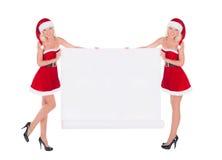 Zwei glückliche nette Sankt-Frauen mit dem Weihnachtsplakat lokalisiert auf whi Lizenzfreies Stockbild