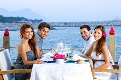 Zwei glückliche Paare, die an der Küste zu Abend essen lizenzfreie stockfotos