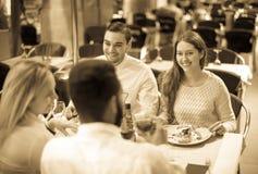 Zwei glückliche Paare, die Restaurant am im Freien sitzen lizenzfreie stockfotos
