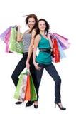 Zwei glückliche schöne Frauen mit Käufen Stockfotografie