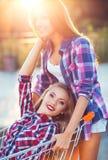 Zwei glückliche schöne jugendlich Mädchen, die draußen Warenkorb fahren Stockbilder