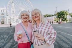 Zwei glückliche schöne weibliche Pensionäre machen Foto auf Quadrat lizenzfreies stockfoto
