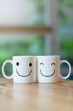 Zwei glückliche Schalen auf hölzerner Tabelle mit bokeh, über Liebeskonzept Lizenzfreie Stockfotografie