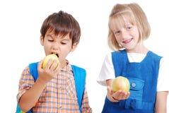 Zwei glückliche Schulkinder, die einen Apfel essen lizenzfreie stockfotografie