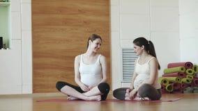 Zwei glückliche schwangere Frauen, die auf Matten sitzen und in der Turnhalle sprechen stock video footage
