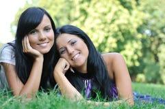 Zwei glückliche Schwestern, die draußen im Gras liegen Stockbild