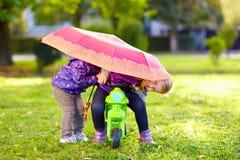 Zwei glückliche Schwestern, die im Herbstpark spielen Stockfoto