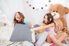 Zwei glückliche Schwestern, die mit Kissen lachen und kämpfen Stockfotografie