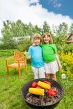 Zwei glückliche Schwestern stehen in der Umarmung nahe BBQ-Grillen Stockbild