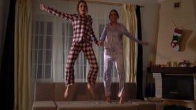 Zwei glückliche Schwesterzwillinge in den pajams, die auf die Couch in einem gemütlichen Wohnzimmer springen und Spaß wie in Kind stock video