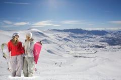 Zwei glückliche Snowboarders im Schnee deckten Berge ab Lizenzfreie Stockfotos