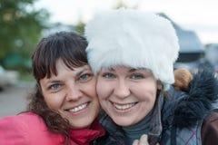 Zwei glückliche umfassende, lehnende Backe zur Backe und lächelnde Frauen, Gesichtsporträt lizenzfreie stockfotos