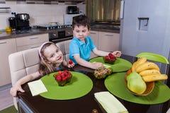Zwei glückliche Vorschulkinder, die gesunde Erdbeere essen Lizenzfreie Stockfotografie