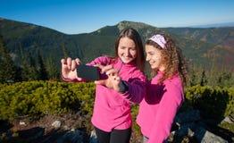 Zwei glückliche weibliche Wanderer, die selfie Foto lächeln und machen stockbilder