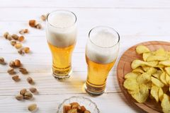 Zwei Glas Bier und Snäcke auf einem weißen Holztisch Chips, Pistazien, trockener Käse stockfotos