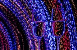 Zwei Glas Champagnerwein auf Hintergrund der Zusammenfassung färbte Lichter in der Bewegung Stockbilder