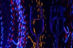 Zwei Glas Champagnerwein auf Hintergrund der Zusammenfassung färbte Lichter in der Bewegung Stockbild