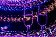 Zwei Glas Champagnerwein auf Hintergrund der Zusammenfassung färbte Lichter in der Bewegung Stockfotografie