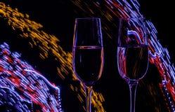 Zwei Glas Champagnerwein auf Hintergrund der Zusammenfassung färbte Lichter in der Bewegung Lizenzfreie Stockfotos