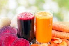 Zwei Glas der frischen roter Rübe und des Karottensaftes, der Rote-Bete-Wurzeln und der Karotten Gemüse auf dem Holztisch, defocu Stockbild