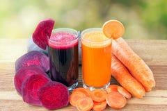 Zwei Glas der frischen roter Rübe und des Karottensaftes, der Rote-Bete-Wurzeln und der Karotten Gemüse auf dem Holztisch, defocu Lizenzfreies Stockbild