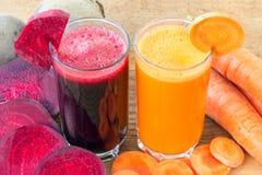 Zwei Glas der frischen roter Rübe und des Karottensaftes, der Rote-Bete-Wurzeln und der Karotten Gemüse auf Holztisch Stockbilder