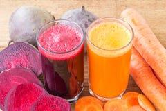Zwei Glas der frischen roter Rübe und des Karottensaftes, der Rote-Bete-Wurzeln und der Karotten Gemüse auf Holztisch Stockfoto
