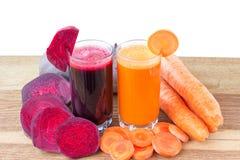 Zwei Glas der frischen roter Rübe und des Karottensaftes, der Rote-Bete-Wurzeln und der Karotten Gemüse auf Holztisch, weißer Hin Stockfoto