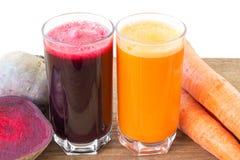 Zwei Glas der frischen roter Rübe und des Karottensaftes, der Rote-Bete-Wurzeln und der Karotten Gemüse auf Holztisch, weißer Hin Stockfotografie