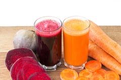 Zwei Glas der frischen roter Rübe und des Karottensaftes, der Rote-Bete-Wurzeln und der Karotten Gemüse auf Holztisch, weißer Hin Lizenzfreies Stockbild