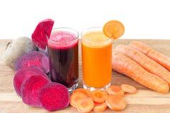 Zwei Glas der frischen roter Rübe und des Karottensaftes, der Rote-Bete-Wurzeln und der Karotten Gemüse auf Holztisch, weißer Hin Stockbild