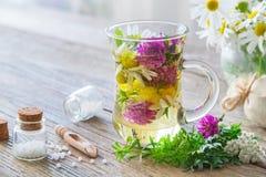 Zwei Glasbecher gesunder Kräutertee oder Infusion, Flaschen homöopathische Kügelchen stockbild
