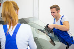 Zwei Glaser oder Mechaniker ersetzen Windschutzscheibe oder Windfang auf Auto Stockbild