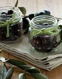 Zwei Glasgläser mit schwarzen Oliven Stockbild