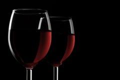 Zwei glassed vom Rotwein, der auf schwarzem Hintergrund getrennt wurde lizenzfreie stockfotos