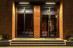 Zwei Glastüren in einem Backsteinbau in der Nacht lizenzfreies stockbild