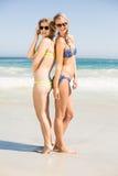 Zwei glückliche Frauen im Bikini und in Sonnenbrille, die zurück zu Rückseite stehen Stockfotos