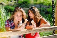 Zwei glückliche Freundinnen, die draußen Eiscreme essen Stockbilder